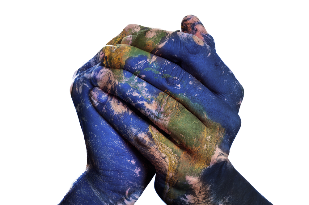 Clasped hands with satellite image of Earth superimposed