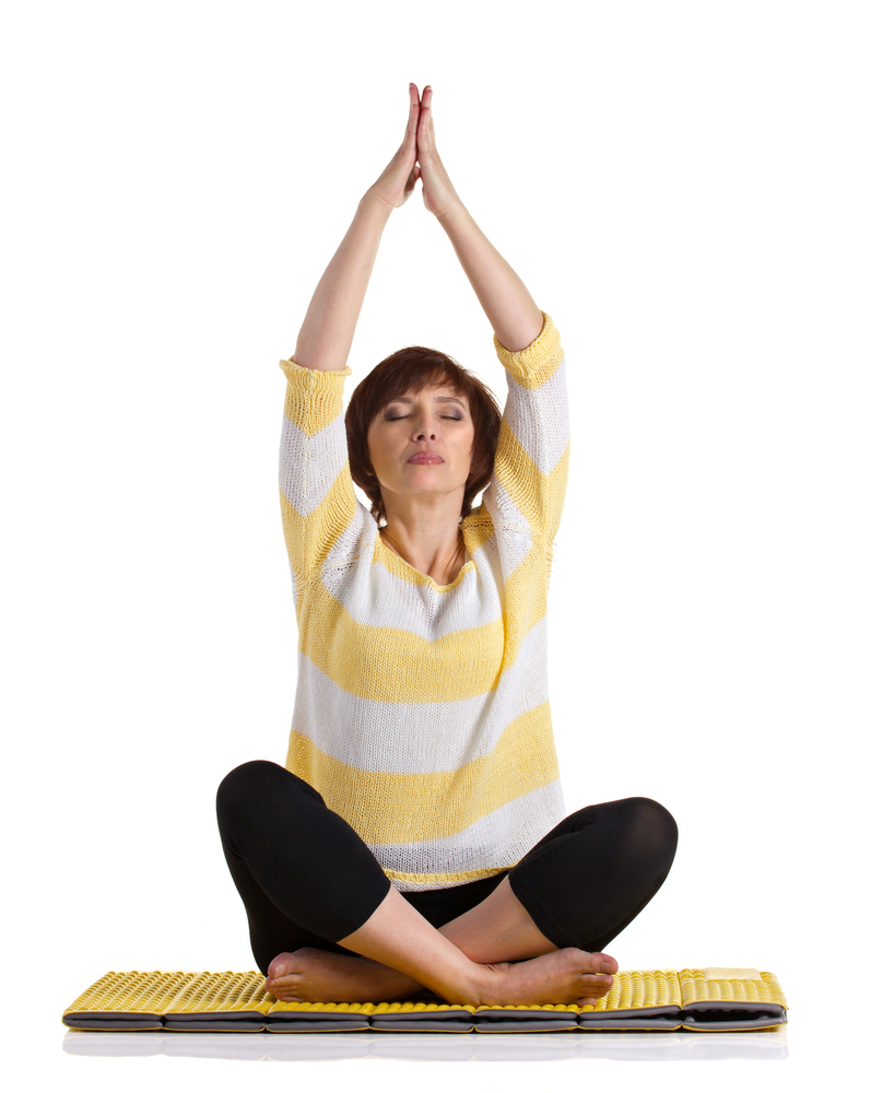 woman in yellow and white striped sweter stretching on yoga mat
