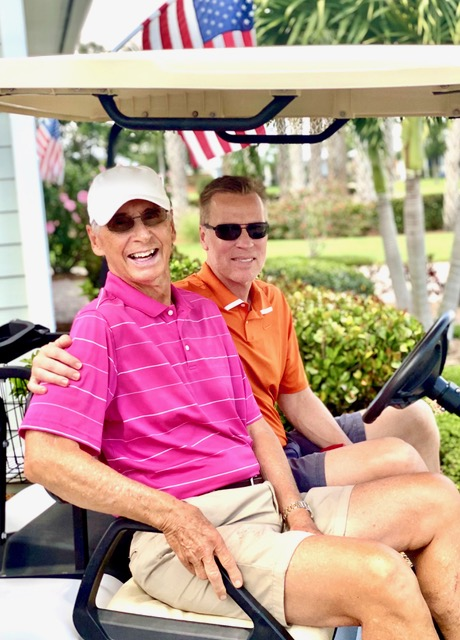 Two men riding a golf cart, smiling at the camera.
